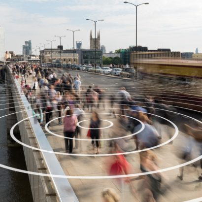 Signal from a phone shown as concentric rings coming from a pedestrian walking on London Bridge.